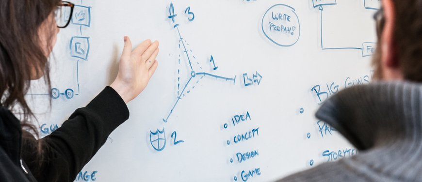 Designers talking design at a whiteboard